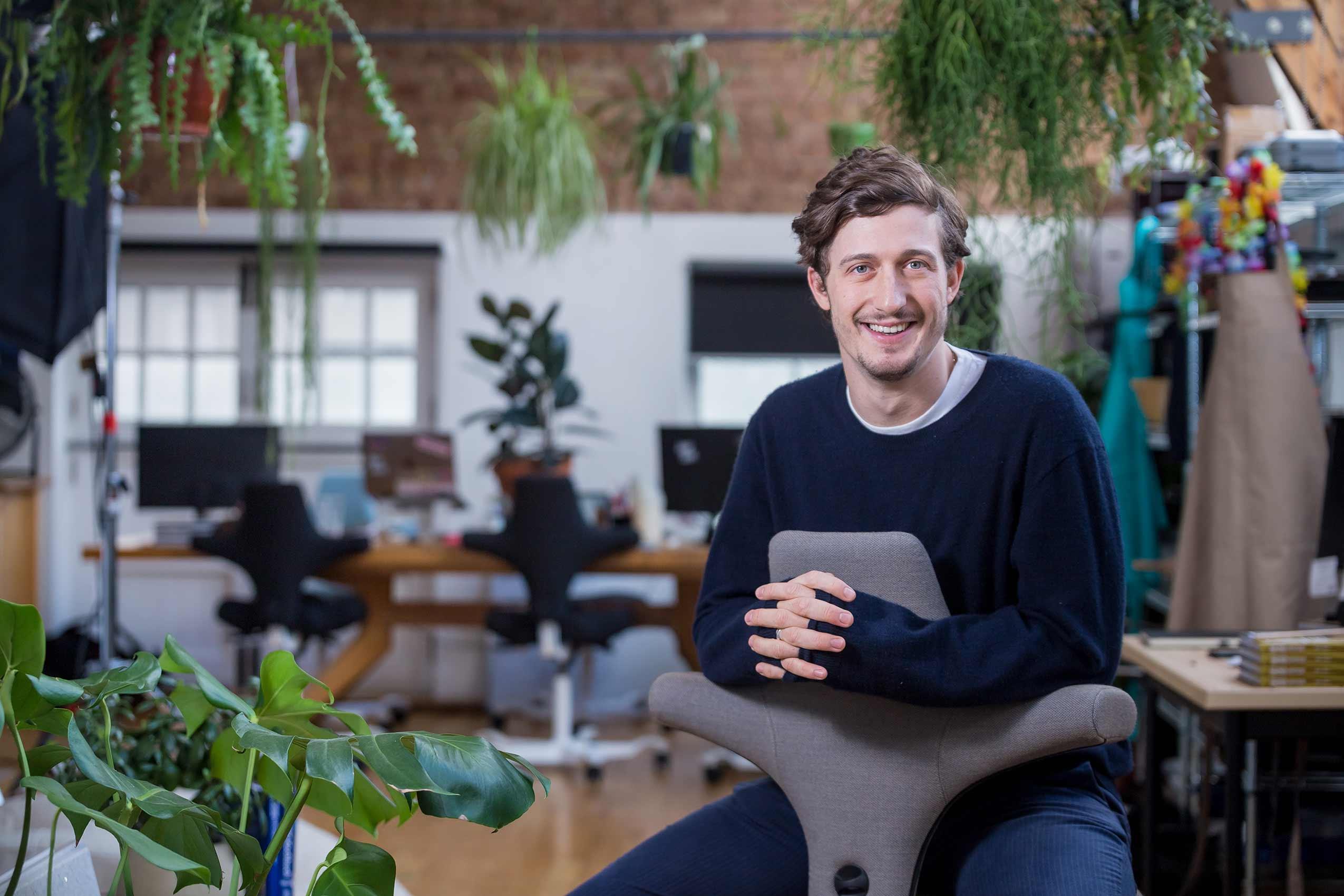 Ben Lebus founder of mob kitchen sitting on a hag capisco chair in kitchen studio
